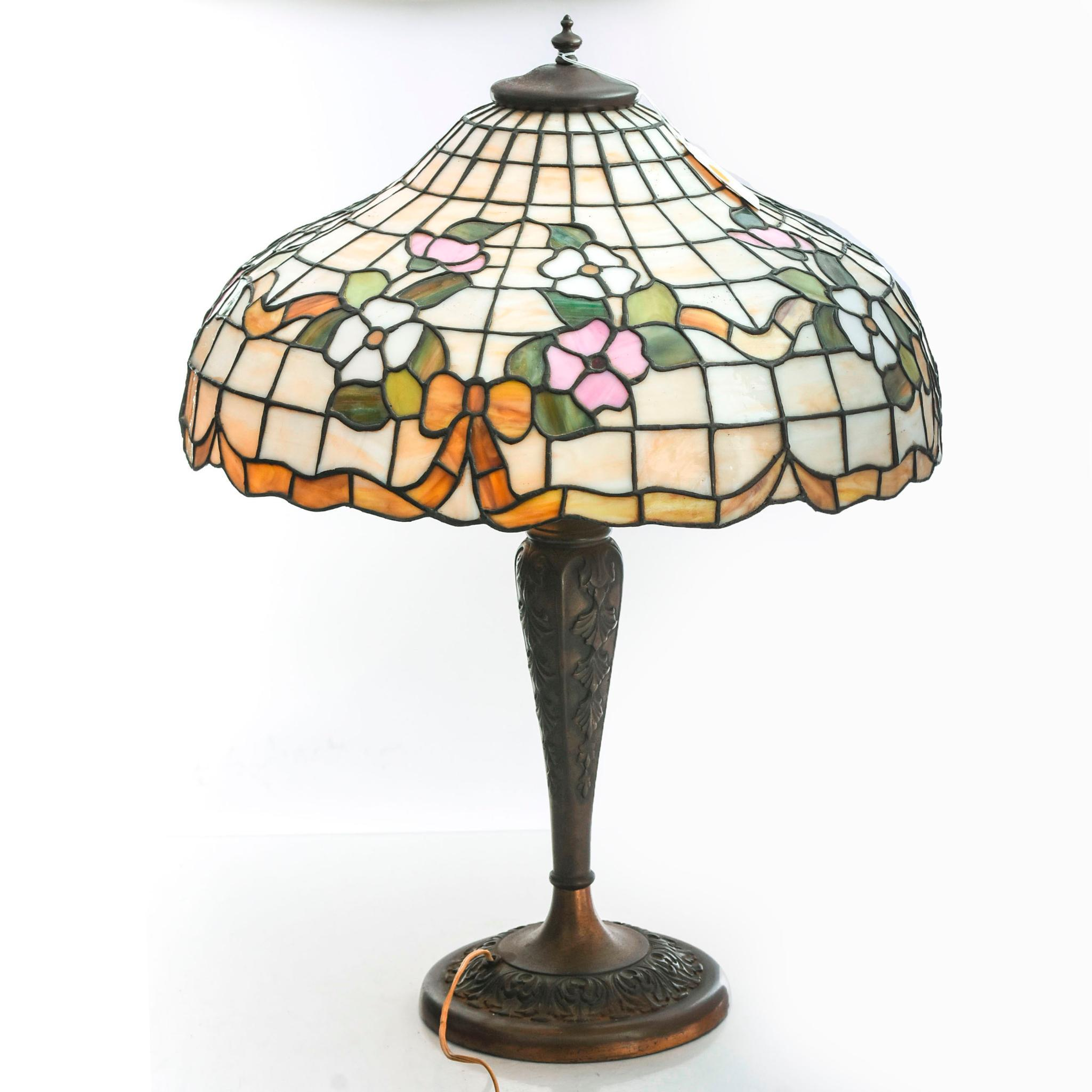 A Tiffany style lamp with bows in orange, pink, green and white colored glass.